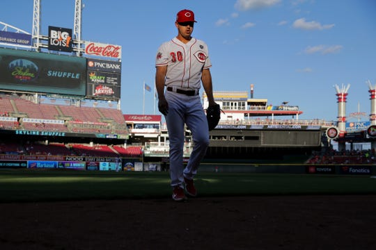 Cincinnati Reds starting pitcher Tyler Mahle (30) exhales as he walks back to the dugout in the third inning of an MLB baseball game against the Milwaukee Brewers, Monday, July 1, 2019, at Great American Ball Park in Cincinnati.