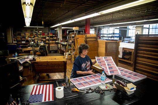 Donna Barnes stacks sheets of mini American flags at The National Flag Company in the West End Tuesday, July 2, 2019. Barnes has worked at The National Flag Company for 32 years.