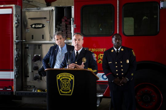Newtown Police Chief Tom Synan speaks at a news conference about efforts to help Ohio communities hit hard by fentanyl overdoses at the Cincinnati Fire Department Engine 35 on Tuesday, July 2, 2019. Sen. Sherrod Brown (left) and EMS District Chief Cedric Wilson (right) listen to Synan's speech.
