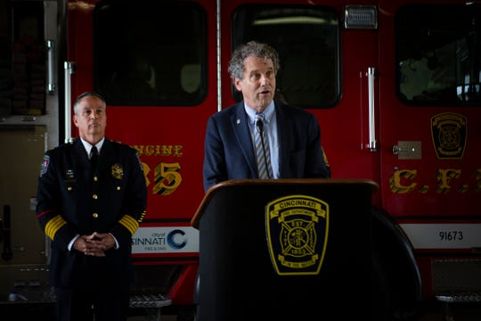 Sen. Sherrod Brown speaks at a news conference about efforts to help Ohio communities hit hard by fentanyl overdoses at the Cincinnati Fire Department Engine 35 on Tuesday, July 2, 2019. City of Newtown Chief Tom Synan (left) listens to Brown's speech.