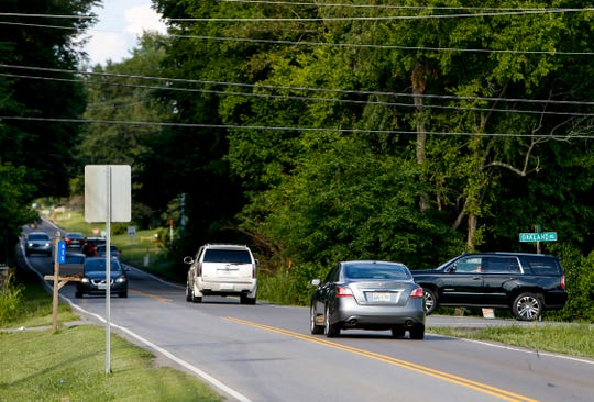 Cars pass by while others wait to enter traffic at the often-crowded intersection at Tylertown and Oakland roads in Clarksville on July 1.