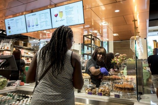 Barista Carla Reaves assists a customer at the new Plum Market on Woodward Avenue in downtown Detroit on Tuesday.