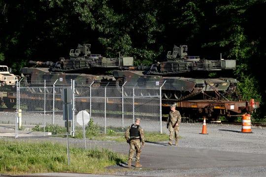 Military police walk near Abrams tanks on a flat car in a rail yard, Monday, July 1, 2019, in Washington.