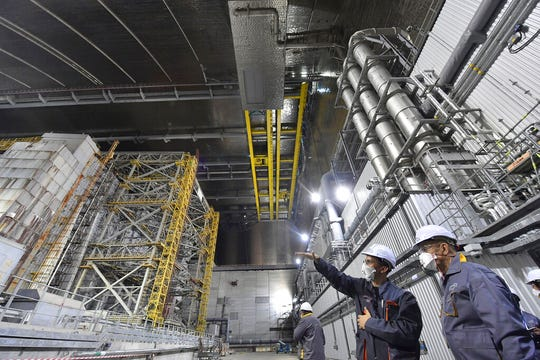 In this June 1, 2019, file photo, French Foreign Minister Jean-Yves Le Drian, right, listens to an employee inside the New Safe Confinement (NSC) movable enclosure at the nuclear power plant in Chernobyl, Ukraine.