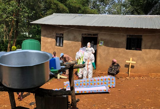 Ebola workers enter a house to decontaminate the body of a woman suspected of dying from Ebola, before the vehicle of the health ministry Ebola response team was attacked in Beni, northeastern Congo Monday, June 24, 2019.