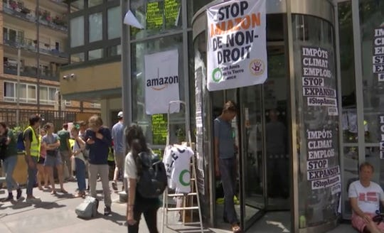 Environmental activists mount a passive protest targeting the Amazon headquarters building in Paris, France, Tuesday July 2, 2019, accusing the online distribution company of destroying jobs and hurting the planet.