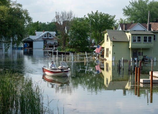 """Boaters travel the canals around the Detroit street called Klenk Island on the far east side. The Detroit River canals that cut through neighborhoods are sometimes called """"Little Venice.""""  They provide a popular route for kayakers."""