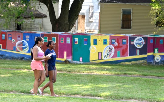 Tiavonni Freeman, left, 16, and her sister, Tyesha, 12, both of Detroit, stroll on the walking path at Alfonso Wells Memorial Park in front of the Birwood Wall, which some neighbors call 'the Detroit Wall.' The wall was built in 1941 as a way to separate black neighbors from white neighbors expected to move into the area.