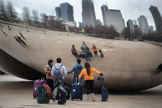 "In 2017, Chicago visitors look over the Cloud Gate or ""The Bean"" sculpture in Millennium Park."