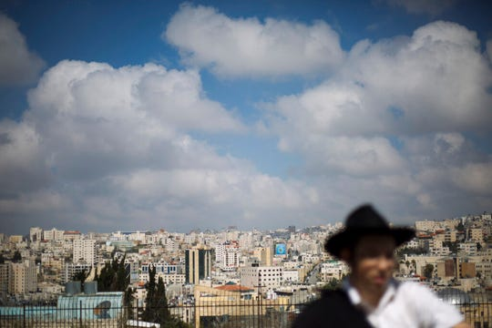 In this Wednesday, March 6, 2019 photo, a Jewish man visits the Israeli controlled part of the West Bank city of Hebron, in the West Bank. The Falic family of Florida, owners of the ubiquitous chain of Duty Free Americas shops, funds a generous and sometimes controversial philanthropic empire in Israel that runs through the corridors of power and stretches deep into the occupied West Bank. An Associated Press investigation shows that the family has donated at least $5.6 million to settler groups in the West Bank and east Jerusalem over the past decade, funding synagogues, schools and social services, along with causes considered extreme even in Israel.
