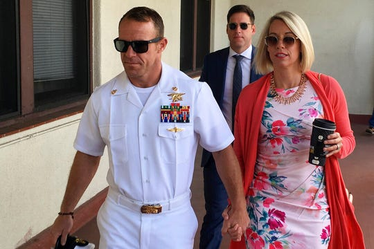 Navy Special Operations Chief Edward Gallagher, left, walks with his wife, Andrea Gallagher as they arrive to military court on Naval Base San Diego, Monday, July 1, 2019, in San Diego. Gallagher was acquitted of premeditated murder Tuesday, July 2, 2019, in the killing of a wounded Islamic State captive under his care in Iraq in 2017.