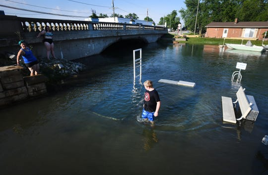 Jack Fitzgerald, 10, walks on a dock that is usually a kayak launch when not under water in downtown Gibraltar on Monday.