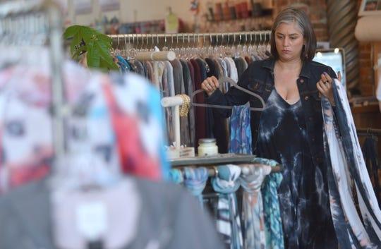 Sales associate Maya Gangadharan, of Royal Oak, arranges scarves for sale.