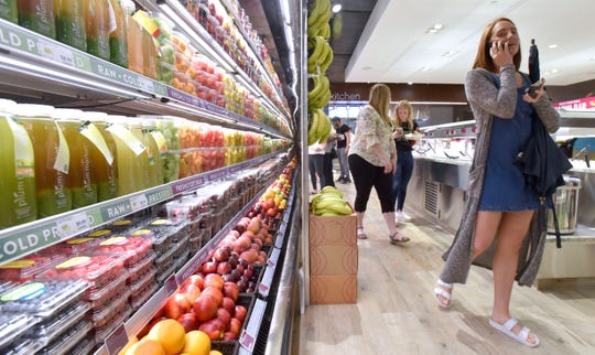 Customers walk past the raw, cold-pressed juices and fresh fruits display.