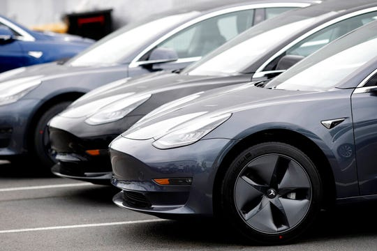In this Sunday, May 19, 2019, file photo, a line of unsold 2019 Model 3 sedans sits at a Tesla dealership in Littleton, Colo.  The electric car and solar panel company said it handed over 95,200 vehicles from April through June, breaking the previous record of 90,700 set in the fourth quarter of last year.
