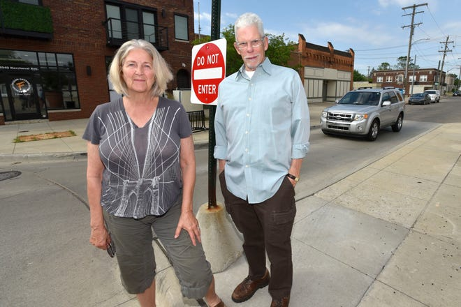 Grosse Pointe Park residents Frank Joyce and his wife, Mary Anne Barnett, pose at the one-way sign where Kercheval enters Wayburn from the west from Detroit to Grosse Pointe Park, but does not allow motorists to enter Detroit from the east in the round about, Tuesday morning, July 2, 2019.