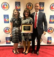 Annie Head, Port Clinton Middle School teacher; Carrie Sanchez, PCMS Principal, and Patrick Adkins, Superintendent of Schools stand together after Sanchez was presented with a National Leadership Award from the National Forum to Accelerate Middle Grade Reform.
