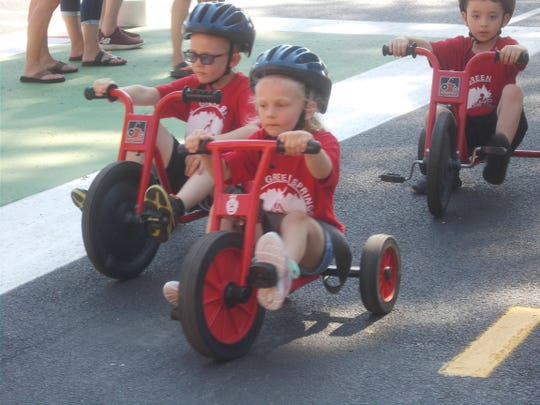 Children ride their Big Wheel bikes on the streets of Clyde's Safety Village.