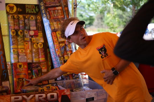 Tre Bradley talk to customers about different fireworks products at his stand on July 2.