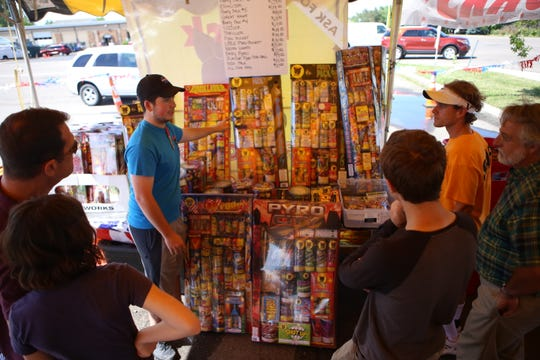 Dallas Brown and Tre Bradley talk to customers about different fireworks products at their stand on July 2.