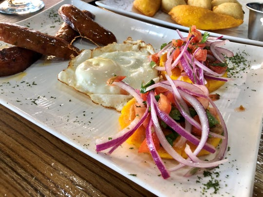 Llapingachos, potato cakes topped in a red-onion-tomato slaw, nod to Ecuador. At Llama's house they came with a fried egg and chorizo sausages for $8.99.
