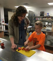 Anna Westmark, community health educator with the Kewaunee County Public Health Department, helps a student slice tomatoes during a nutrition and cooking class offered by the department in June at Algoma Middle School.