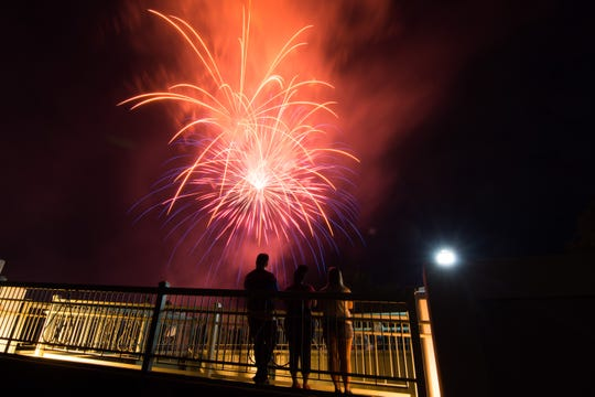 Spectators watch fireworks from a pedestrian bridge on the University of Iowa campus. Sunday, July 3, 2016.