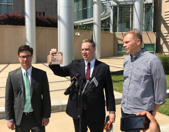 "Justin Pearson holds a piece of packaging from Upton's Naturals, while Aaron Rice (left), from the Mississippi Justice Institute, and Dan Staackmann (right), founder of Upton's Naturals, look on. The trio held a press conference about a lawsuit filed in response to a Mississippi law that bans food labels such as ""veggie burger."""