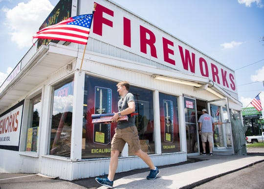 Customer Wesley Kirkland of Knoxville carries the last of his fireworks order to his car outside Dixie Lee Fireworks in Lenoir City on Tuesday, July 2, 2019.