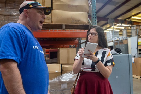 Reporter Leigh Guidry speaks with Ryan Demengeaux as volunteers work at the Lafayette Parish School System warehouse, stuffing backpacks with school supplies to be donated to thousands of students at eight Lafayette Parish schools as part of the Love Our Schools initiative. Through the program, nearly 5,000 students will receive backpacks filled with school supplies.  Tuesday, July 2, 2019.