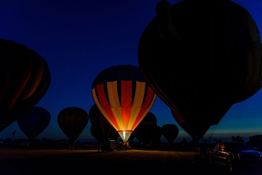 ground level view of hot air balloons glowing at night from flame torch
