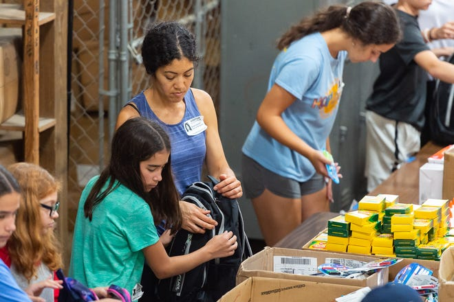 Anna Osland organizes supplies to be added to backpacks as volunteers work at the Lafayette Parish School System warehouse to stuff backpacks with school supplies to be donated to thousands of students at eight Lafayette Parish schools as part of the Love Our Schools initiative. Tuesday, July 2, 2019.