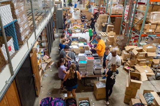 Volunteers stuff backpacks full of school supplies at the Lafayette Parish School System warehouse. The backpacks will be donated to thousands of students at eight Lafayette Parish schools as part of the Love Our Schools initiative.  Tuesday, July 2, 2019.