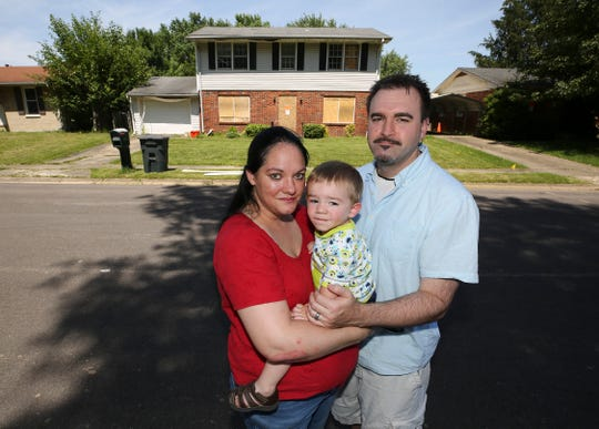 Kendall and Anna Browning stand in front of their home on Assembly Road in Jeffersonville with their 19-month-old son, Rowan. The house is boarded up and condemned following an explosion in the neighborhood that disintegrated a neighbor's home, killing one person and injuring another.  June 27, 2019