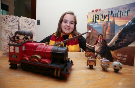 Harry Potter fan Annika Olsen, 11, with some of her collectibles.  Her parents are members of the Louisville Orchestra and will be performing music that accompanies the production of Harry Potter and the Goblet of Fire at the Kentucky Center for the Performing Arts.