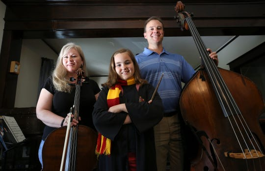 Allison Olsen, left, and her husband Karl Olsen, right, pose with their daughter Annika Olsen, 11, at their home.  Allison plays the cello and Karl plays the bass.   Annika is a Harry Potter fan.  Her parents are members of the Louisville Orchestra and will be performing music that accompanies the production of Harry Potter and the Goblet of Fire at the Kentucky Center for the Performing Arts.