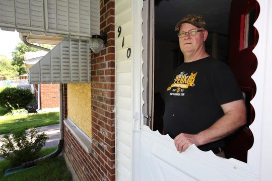 David White stands in the doorway of his home on Assembly Road in Jeffersonville inside an opening that use to have plexiglass. The plexiglass was damaged following an explosion in the neighborhood that destroyed a neighbor's home and killed one person and injured another. He removed the rest of the plexiglass and another damaged window, to the left, has been boarded up. June 27, 2019