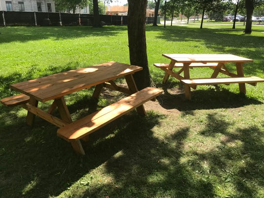A group called Punks with Lunch recently placed four picnic tables in downtown Lansing's Reutter Park. Members locked them to trees. City officials don't have plans to remove them.
