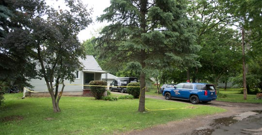 Members of the Michigan State Police and Lansing Police Department's Crime Scene Investigation Unit seen working in the backyard of a home in the 800 block of Loa St. in Lansing, Tuesday, July 2, 2019.