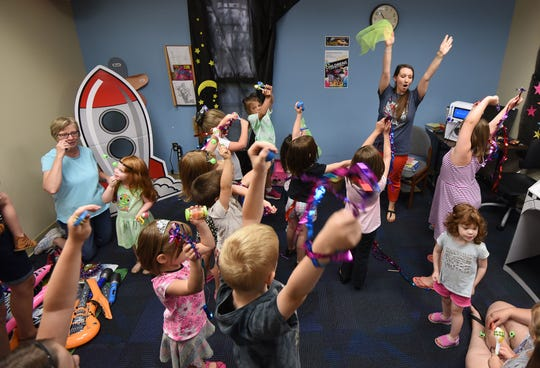 Children's librarian Brindi Bays leads a song and dance during the Glow-in-the-Dark Dance Party at Madison branch of the Mansfield/Richland County Library.