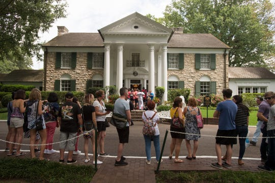 Fans wait in line outside Graceland, Elvis Presley's Memphis home, on Aug. 15, 2017, in Memphis. Fans from around the world were at Graceland for the 40th anniversary of his death. Presley died Aug. 16, 1977.