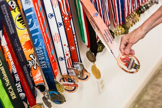 Kay DiBianca holds a medal from the Birmingham, Alabama National Senior Games on display in the DiBianca's home in Memphis on July 1, 2019. Every two years the Senior Games give people over 50 a chance to compete in Olympic style events. Kay, 73, entered the games in 2013 while her husband, Frank, 79, began competing in the games in 2015.