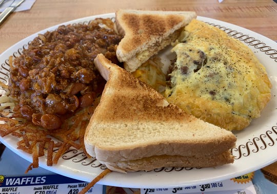 A bacon, sausage and cheese omelet with has browns covered in cheese and chili from Waffle House, Naples.