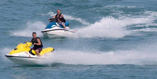 A pair of men riding personal watercraft frolic on Lake Michigan.