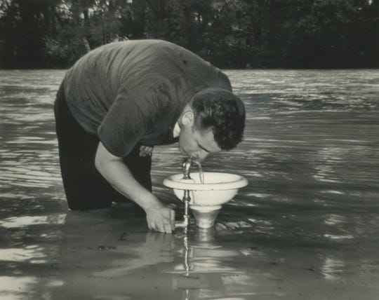 1964: More than knee deep in water, Harlan Krubsack bends over to drink from a bubbler in the Menomonee River Parkway in Wauwatosa on July 18, 1964. The river overflowed its banks after a storm dropped more than 4 inches of rain on the Milwaukee area in an 18-hour period. This photo was on the front page of the July 19, 1964, Milwaukee Journal.