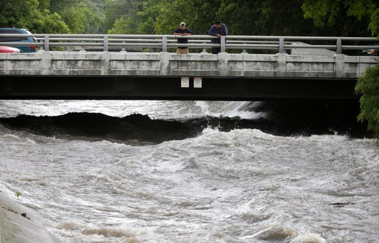 2016: Pedestrians watch the raging waters in the Kinnickinnic River nearly reach the bridge at West Harrison Avenue and South 13th Street on Aug. 30, 2016. A flash flood caused problems that day across the Milwaukee area.