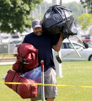Jason Webb of Milwaukee hauls his grill, a tent and supplies from his car to his camping area while setting up for the fireworks display at Veterans Park.