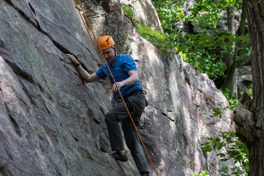 Timothy Hoehnke climbs a route on the West Bluff at Devil's Lake State Park during a rock climbing trip with First Descents on June 22, 2019.
