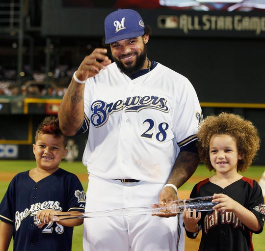 Milwaukee Brewers' Prince Fielder and his sons Jadyn (R) and Haven hold his All-Star Game MVP trophy after Major League Baseball's All-Star Game in Phoenix, Arizona July 12, 2011.