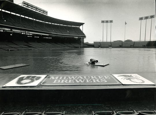 1986: Peter Zettel, an employee of Sportservice Inc., paddles around the infield of County Stadium on a safety cushion that had been washed off the outfield fence during a monstrous rainstorm on Aug. 6, 1986. Water was about 3 1/2 feet deep on the field; fortunately, the Brewers were playing the Yankees in New York City that day.  In the storm, nearly 7 inches of rain swamped much of Milwaukee; two people drowned. This photo was in the Aug. 7, 1986, Milwaukee Sentinel.